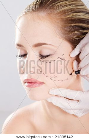 doctor draw correction lines on woman face. Before plastic surgery