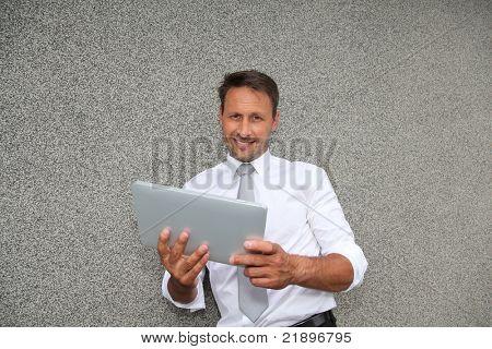 Smiling salesman using electronic tablet