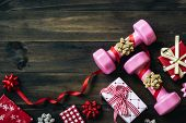 Pink Sport Dumbbells And Gift Bow On White Wooden Background, Merry Christmas And Happy New Year Wis poster