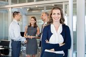 Portrait of executive businesswoman standing in office while team working in background. Smiling bus poster