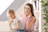 Busy young woman with daughter in home office poster