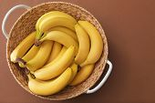 Basket with tasty ripe bananas on color background poster