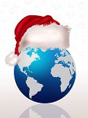 stock photo of world-globe  - Blue world globe with red santa claus cap - JPG