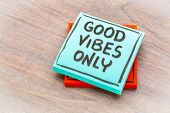 Good vibes only reminder - handwriting on a sticky note against grained wood poster
