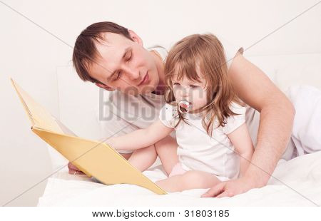 happy family,  father  and daughter reading a book  in bed at home