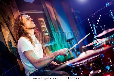 musician playing drums on a red background