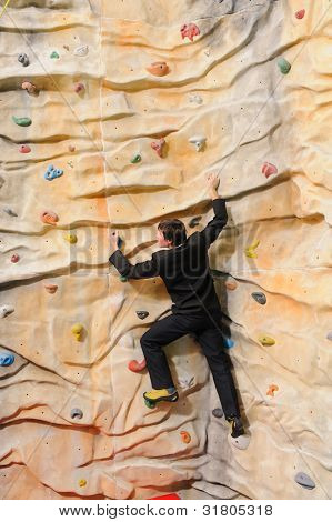 active young business man on rock wall in sport center