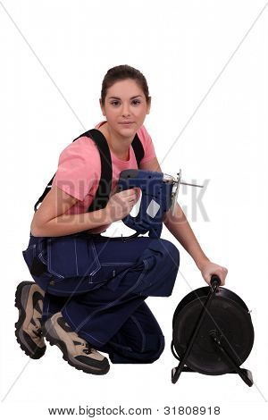 Handywoman holding a jigsaw and an extension cord