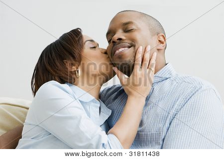 African American woman kissing husband on cheek