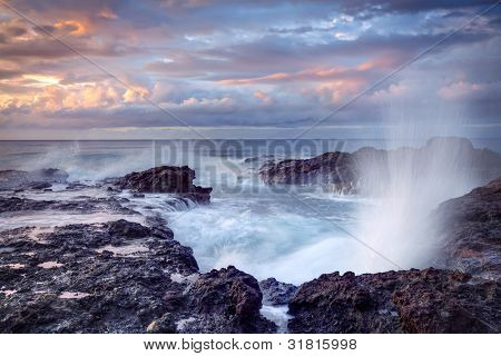 Scenic view of blowhole on rocky coastline with sunset cloudscape background, Reunion Island.