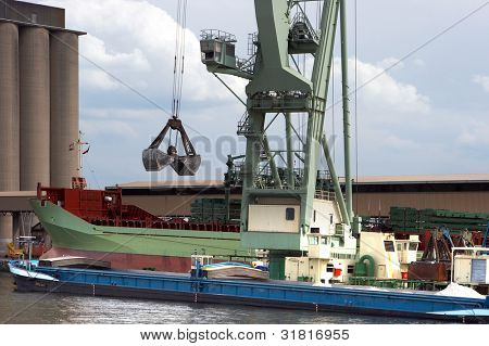 Huge mobile crane floating in Antwerp harbor and loading a ship, this crane is able to lift 800 ton.