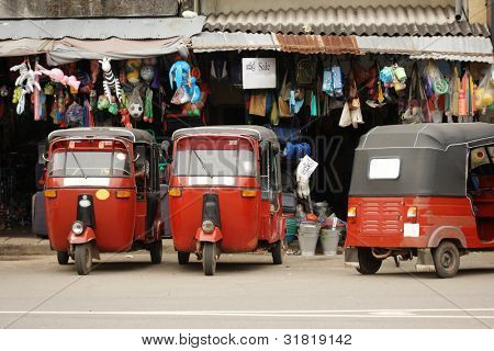 Red tuk-tuk lined up in Ceylon