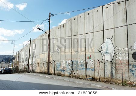 The Israeli separation wall juts into the Palestinian. Graffiti by protesters of the barrier.