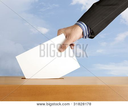 Hand with ballot and box on sky