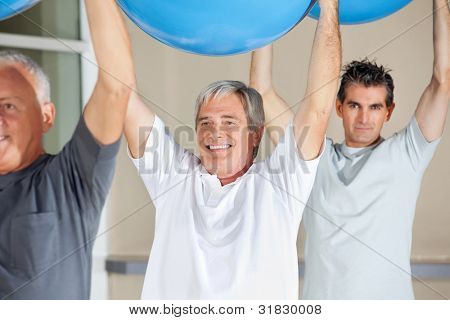 Senior citizens doing back exercises with gym balls in fitness center