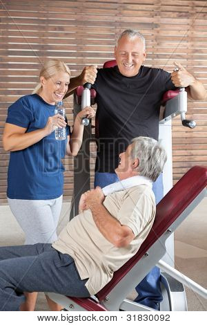 Happy seniors talking in a break in a fitness center