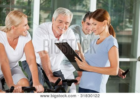 Fitness trainer talking to senior citizens on bikes in gym