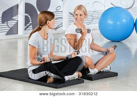 Two senior women doing dumbbell training exercises in gym