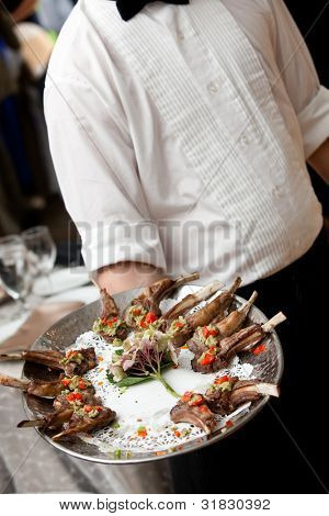 a waiter serving appetizers on a platter during a catered event