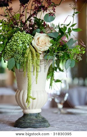 A floral wedding centerpiece on a table during a catered event