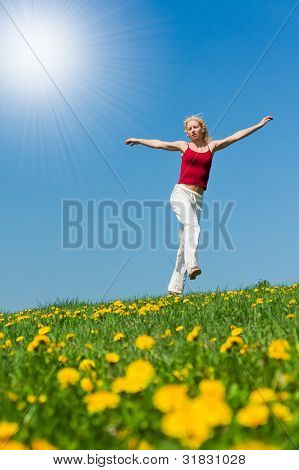 young woman having fun on a flowery meadow