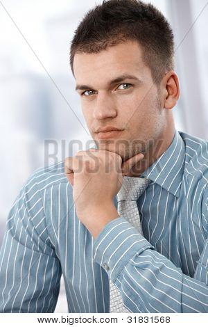Portrait of serious businessman, sitting.