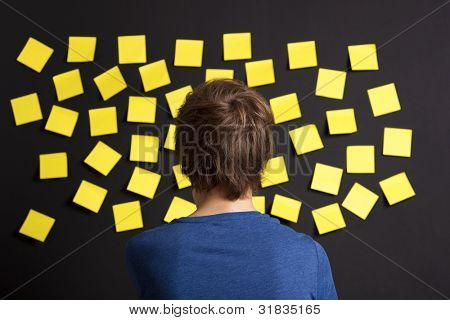Young student looking to a board full of yellow notes