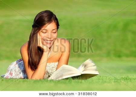 Reading. Woman reading book in park during spring / summer time. Happy smiling beautiful young university student studying lying down in grass. Mixed race Asian Chinese Caucasian female model outdoors