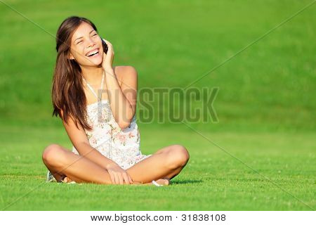 Phone woman laughing in talking in smart phone in park during spring / summer. Happy smiling beautiful young woman sitting in grass. Multiracial Caucasian / Chinese Asian female model outside in dress