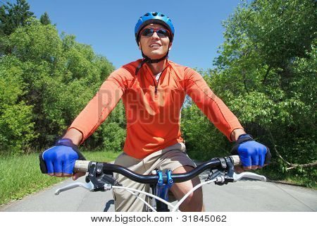 Portrait of a handsome man riding bike in park