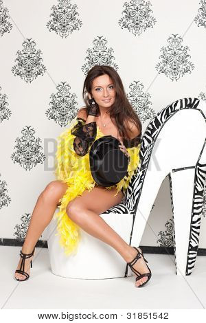 Glamoured portrait of fancy cabare dancer sits on high heel shoe