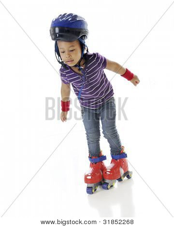 An adorable preschooler unsteady on her plastic roller blades.  On a white background.