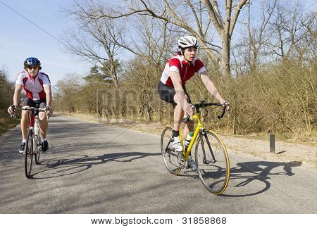 Two cyclists overtaking on a small rural road