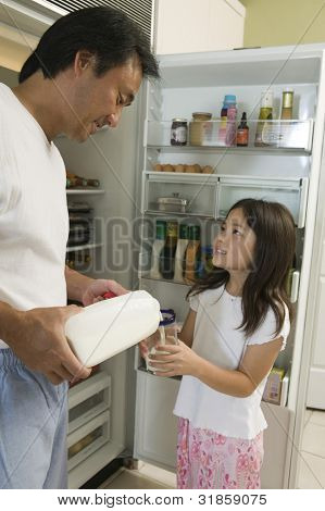 Father Pouring Milk For Daughter