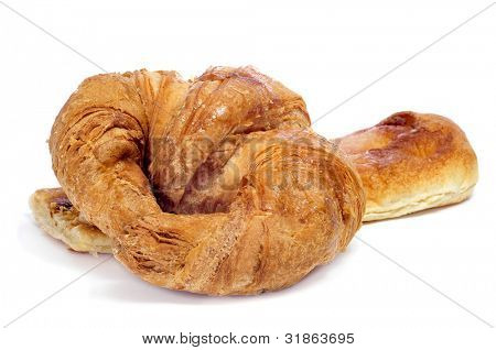 closeup of a croissant and a slice of coca amb sucre on a white background