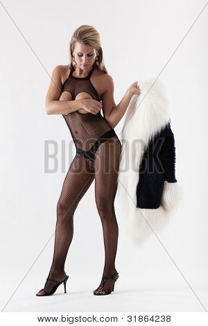 Attractive woman in sexy fishnet lingerie holding fur coat