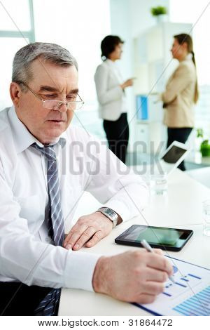 Mature businessman checking the business data presented in graphs