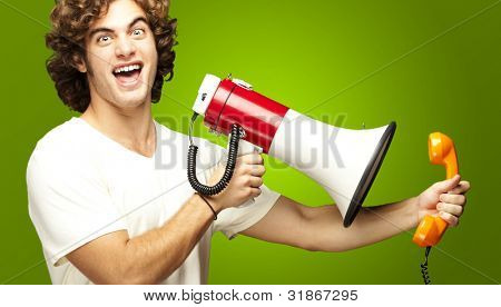 portrait of young man shouting with megaphone and talking on vintage telephone over green