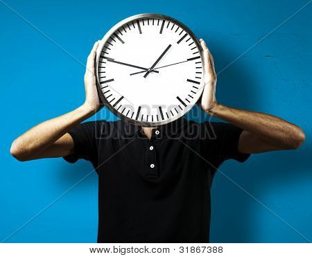 young man holding big clock covering his face over white