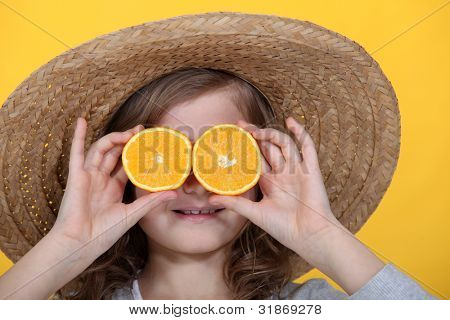 Young girl holding orange slices in front of her eyes