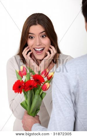 Surprised woman receiving flowers from her boyfriend