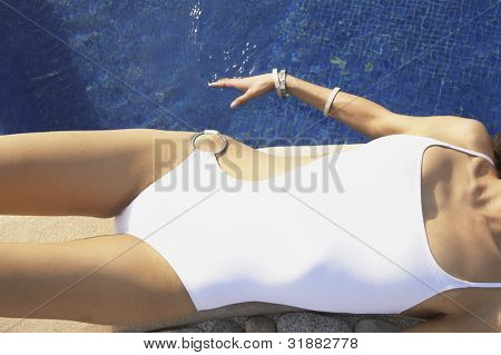 Mulher deitada na borda da piscina do hotel