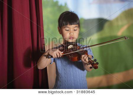 Young Asian girl playing violin at recital