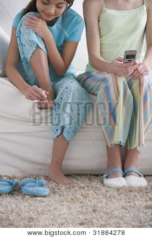 Girls painting toenails and holding cell phone