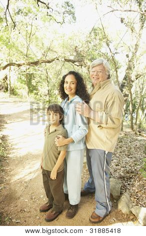 Hispanic grandparents with grandson on nature trail