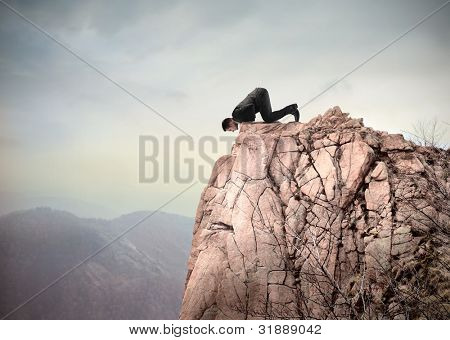 Young businessman kneeling on a mountain peak and looking downwards