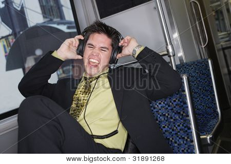 Businessman listening to headphones on a train