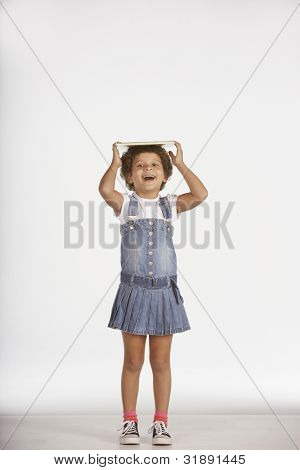 Portrait of girl balancing book on head
