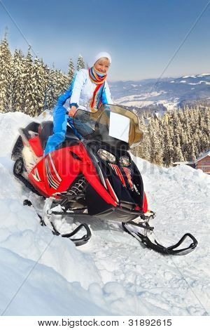 Smiling young woman riding a snowmobile against winter landscape