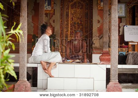 BALI, INDONESIA - MARCH 28: Hindu Brahmin before start ceremonies of Oton - is the first ceremony for baby's on which the infant is allowed to touch the ground on March 28, 2012 on Bali, Indonesia.